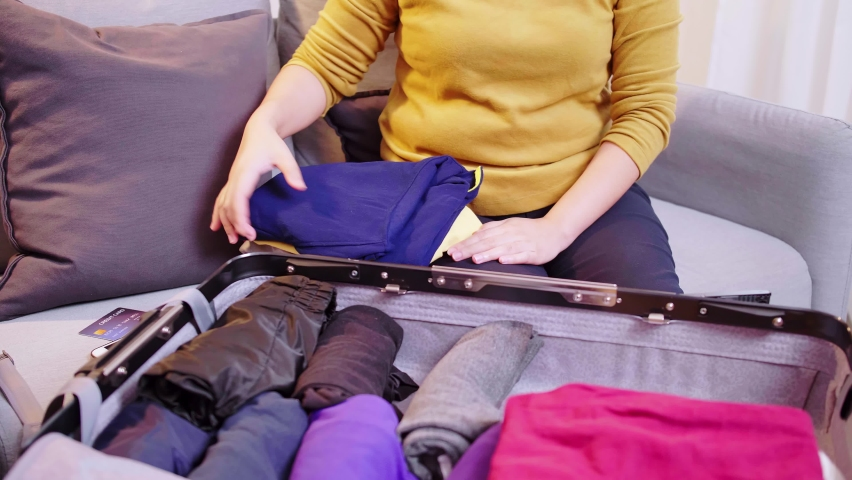 Woman preparing suitcase with clothes for travel. Booking a ticket using a credit card. Royalty-Free Stock Footage #1075947995