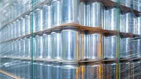 Big stack of aluminum beer cans in brewery. New unused 500 ml aluminium containers for cold beverages packed on pallet rack in supermarket