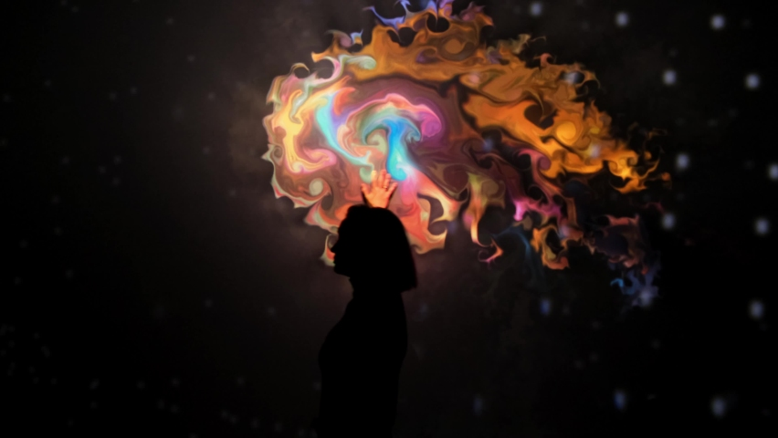 Girl plays with an interactive video installation. New art form, generative graphics. Silhouette of girl draws with her hands in multicolored colors interactive installation on wall | Shutterstock HD Video #1076057936