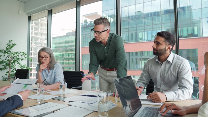 Executive team business people listening to ceo negotiating discussing project results at board meeting. Multicultural professional company leaders working sitting at boardroom table in office. Royalty-Free Stock Footage #1076059682