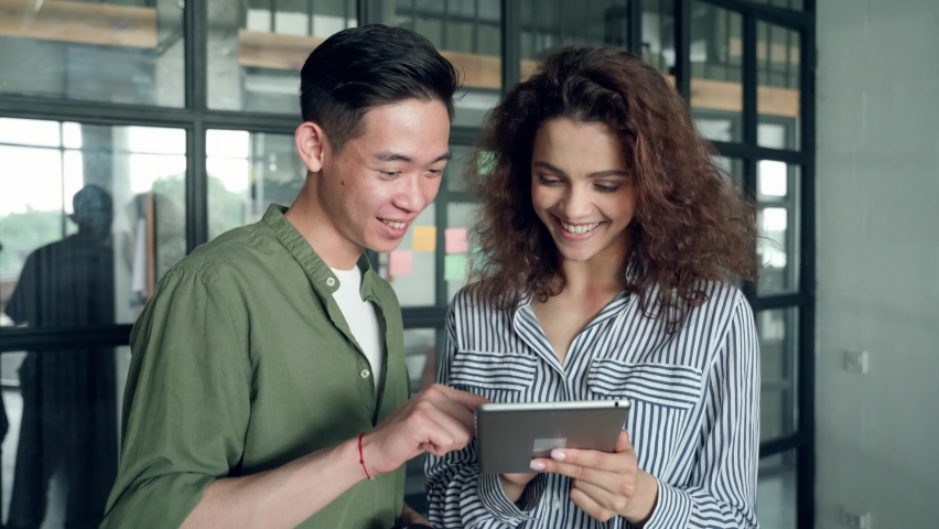 Gen z millennial teenagers Asian guy and latin Hispanic girl using mobile cell phone applications. Diverse high school students testing startup business develop project. Collaborate diversity concept. Royalty-Free Stock Footage #1076060036