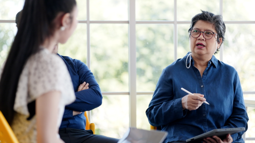 Asian Senior businesswoman meeting to discuss work plans with team members Brainstorming in the meeting room. Consulting on ideas, finance, business investment. happiness at work Royalty-Free Stock Footage #1076089304