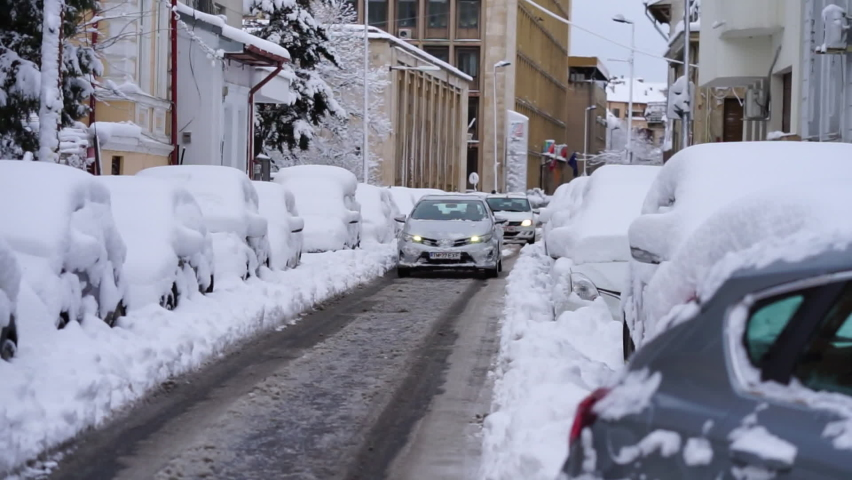 Snowy cars in the morning. Winter season and icy cars on the road in Bucharest, Romania, 2021