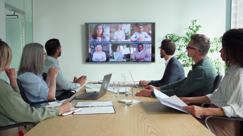 Diverse company employees having online business conference video call on tv screen monitor in board meeting room. Videoconference presentation, global virtual group corporate training concept. Royalty-Free Stock Footage #1076130974