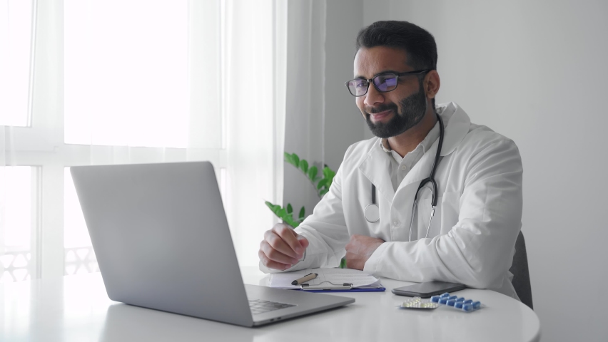 Middle age adult indian man physician doctor wearing white coat video calling distant patient on laptop. Professional medical specialist talking to client using virtual chat computer app. Telemedicine   Shutterstock HD Video #1076190743