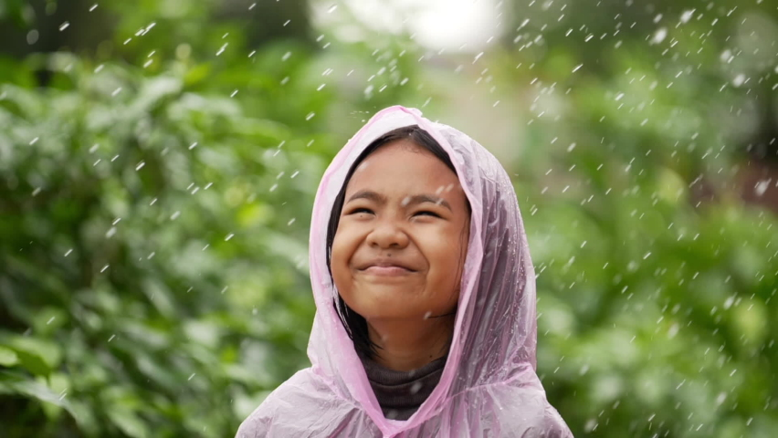 Portrait of Funny girl wears raincoat in rain. Happy asian little girl enjoying the rain dressed in garden. Cheerful, excited girl having fun, wet under rain. Royalty-Free Stock Footage #1076195951