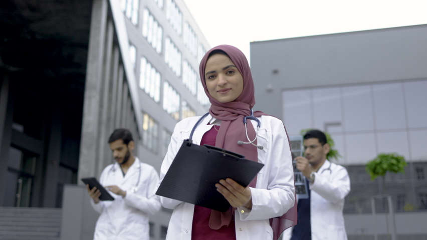 Female Muslim pleasant doctor in hijab, standing with clipboard outdoors in front of hospital building, while two handsome Arabian men doctors working with x-ray and tablet pc behind Royalty-Free Stock Footage #1076196242