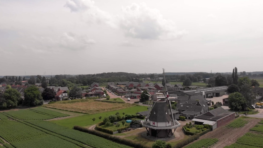 Aerial sideways panning showing typical Dutch windmill with wicks in countryside of The Netherlands in flat agrarian landscape Royalty-Free Stock Footage #1076227472