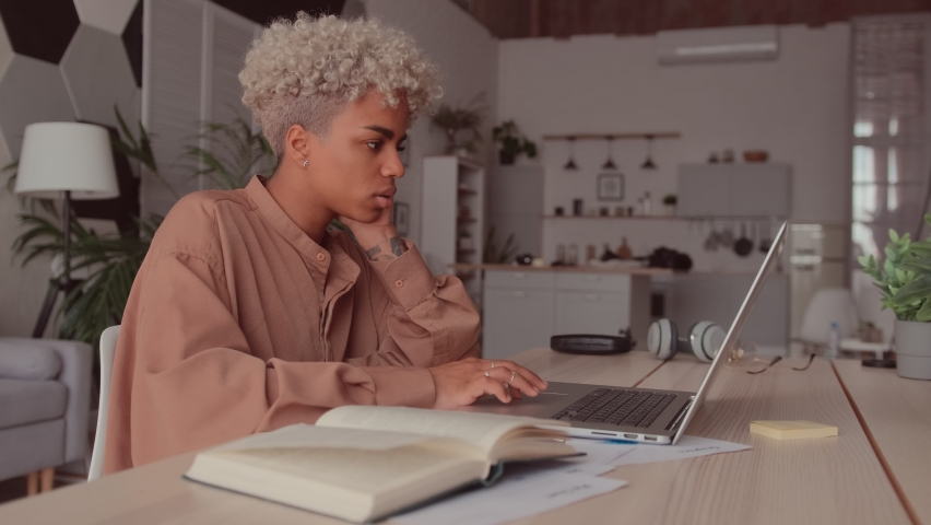 Serious African American student woman studying hard prepares for high school exams, university admission, writing text, using educational material heap of subject textbooks. Self education concept Royalty-Free Stock Footage #1076507744