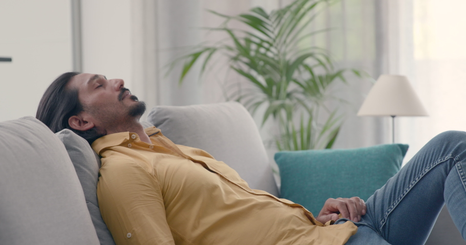 Man sits on the couch at home, he unties his hair and rests with eyes closed