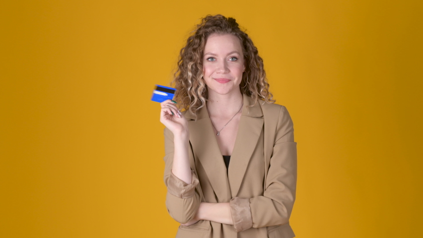 Happy Cheerful young girl with curly hair Point hand on credit bank card showing thumb up like gesture isolated on yellow studio background. People lifestyle concept. Royalty-Free Stock Footage #1076544920