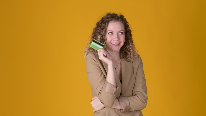 Happy Cheerful young girl with curly hair holds a credit bank card in her hand and dreams isolated on yellow studio background. People lifestyle concept. Royalty-Free Stock Footage #1076544935