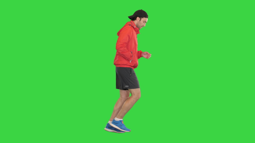 Young man running in a windbreaker on a Green Screen, Chroma Key.