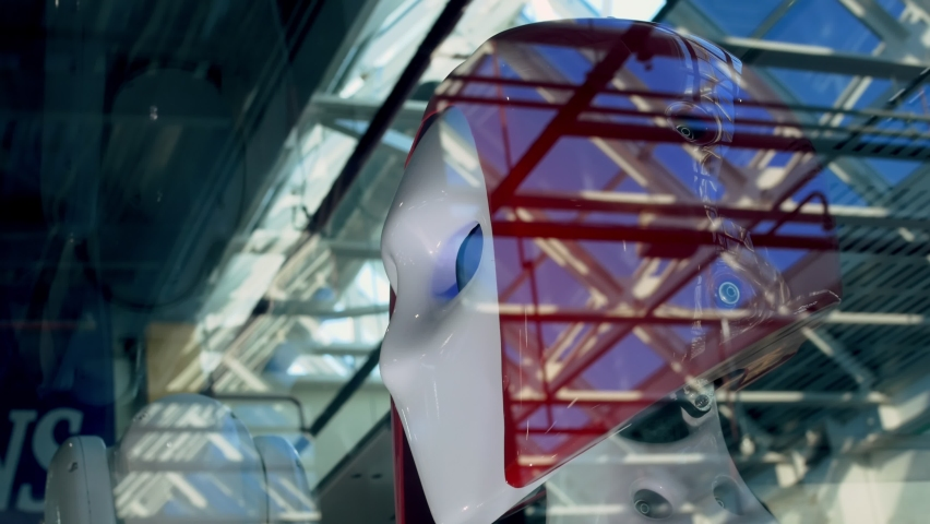 Through the glass you can see the head of a robot with red hair and blue eyes. Through the glass you can see the room in which there are two automatic devices designed for mechanical operations.   Shutterstock HD Video #1076667188