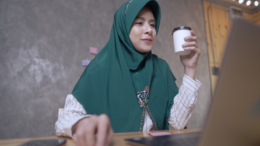 A beautiful Muslim woman video chatting with friend using computer or laptop, cheerfully greeting waving hand, sharing weekday stories on covid-19 pandemic outbreak, distant communication, coffee time Royalty-Free Stock Footage #1076746184