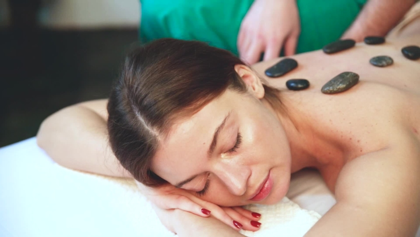A beautiful girl lies on her stomach during a stone massage.   Shutterstock HD Video #1076767040