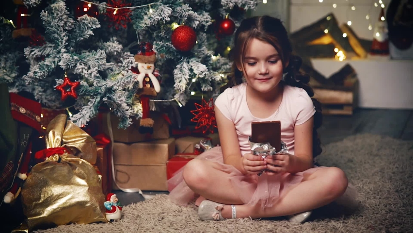 The girl is eating a chocolate bar under the Christmas tree.   Shutterstock HD Video #1076767187