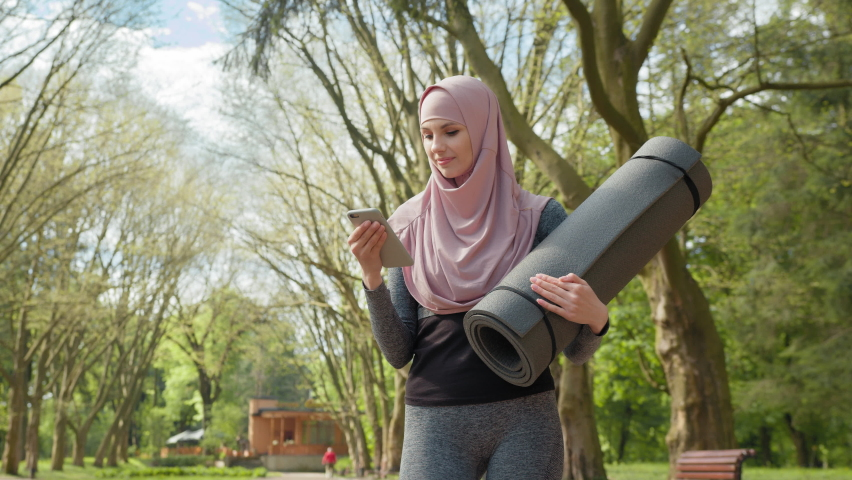 Beautiful young woman in hijab standing at green park with yoga mat and using modern smartphone. Muslim lady in sport clothes resting during workout in fresh air. Woman in hijab using smartphone   Shutterstock HD Video #1076769200