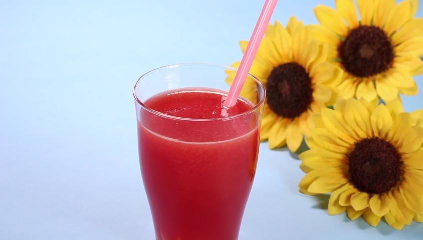 A glass of watermelon juice and sunflower | Shutterstock HD Video #1076794535