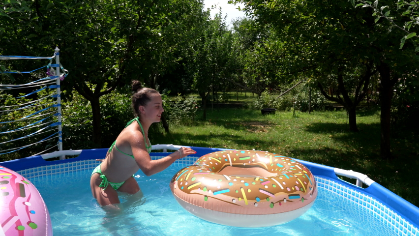 Happy girl kid have fun jumping over donut pool float on sunny summer day, buoyancy | Shutterstock HD Video #1076796521