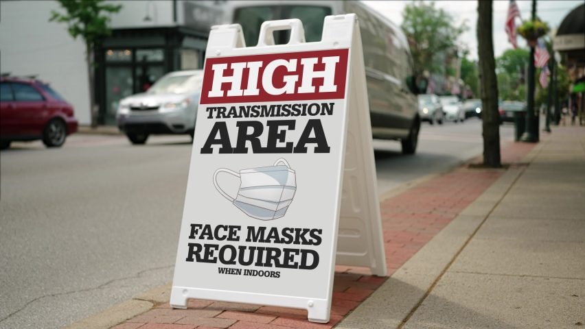 """A sign on the sidewalk on a small town's main street warns people that this is a """"high transmission"""" area for COVID-19. The CDC again required face masks when the delta variant surged in 2021. 