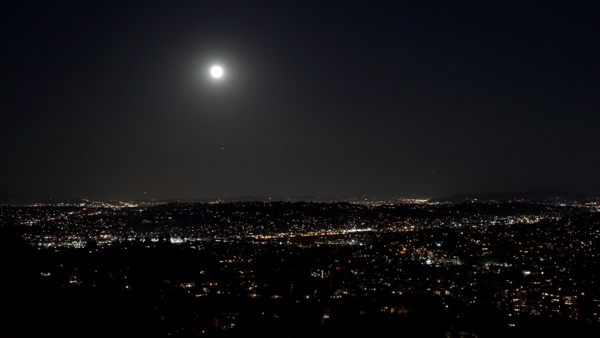 Panoramic view of night city and sky with moon and twinkling stars, night illuminated panorama. | Shutterstock HD Video #1076892344