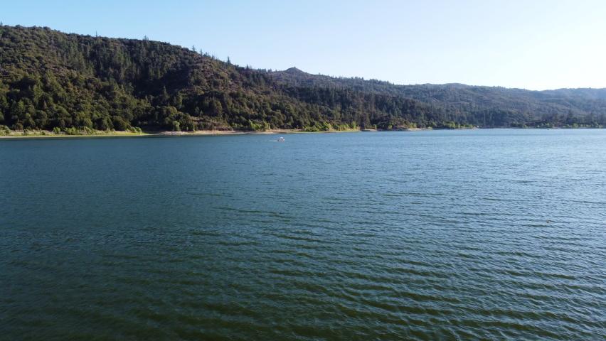 Lonely boat speeding through lake Hemet in aerial drone view | Shutterstock HD Video #1076917697