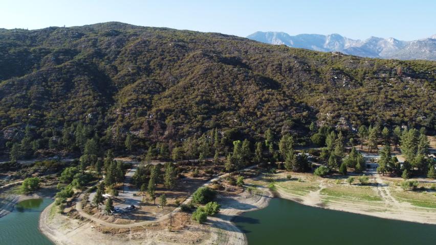 Mountain covered in dense forest near coastline of lake Hemet, aerial view | Shutterstock HD Video #1076917703