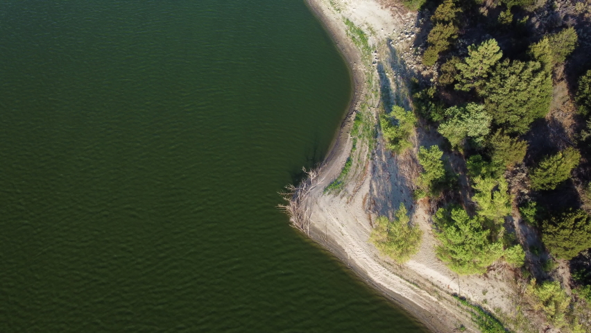 Sandy beach coastline of lake Hemet with dense forest. Aerial top down view | Shutterstock HD Video #1076918063