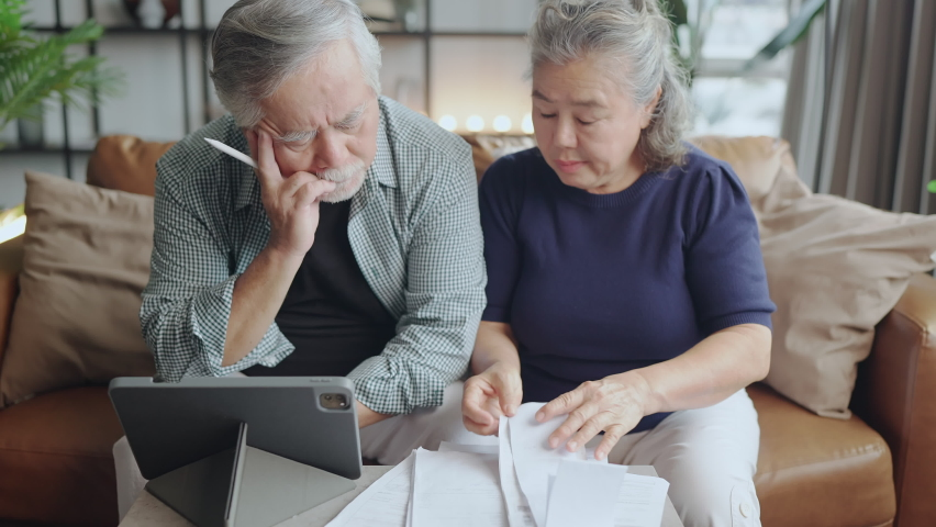 Old retired asian senior couple checking and calculate financial billing together on sofa involved in financial paperwork, paying taxes online using e-banking laptop at living room home background