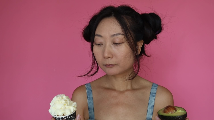 Beautiful Asian Woman Holding Avocado And Sweets Cake And Choosing On Pink Background. Diabetes Concept. | Shutterstock HD Video #1077076058
