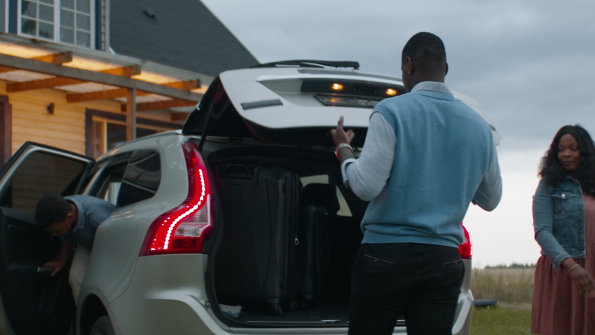 Happy African American family of three arriving by car to their new house. Shot with 2x anamorphic lens