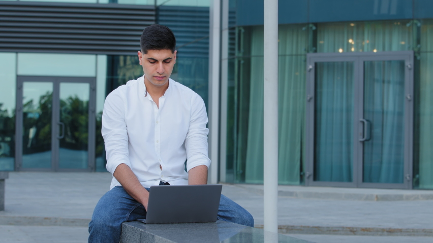 Focused Indian young businessman working on project, using portable laptop sitting outdoors. Concentrated male professional writes new article, prepares report or summary, distance learning concept Royalty-Free Stock Footage #1077268139
