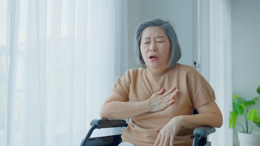 Asian Senior old disabled woman suffer from heart attack on wheelchair. Elder female with chest pain has difficulty breath clutching her chest from acute pain. Hospital Healthcare and medical concept. | Shutterstock HD Video #1077269951