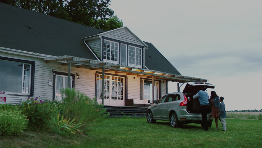 HANDHELD WIDE Happy African American family of arriving by car to their new house. Shot with 2x anamorphic lens