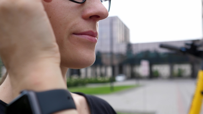 Pensive serious young woman gnaws at the bow of her glasses and looks away, thinks about solving a problem and task, close-up. Stress solving a problem Royalty-Free Stock Footage #1077397790