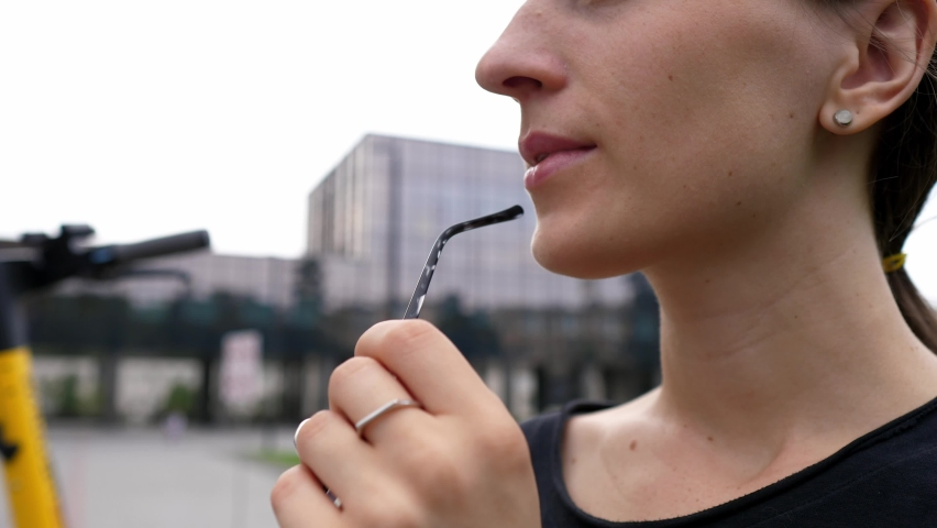 Pensive serious young woman gnaws at the bow of her glasses and looks away, thinks about solving a problem and task, close-up. Stress solving a problem Royalty-Free Stock Footage #1077397793