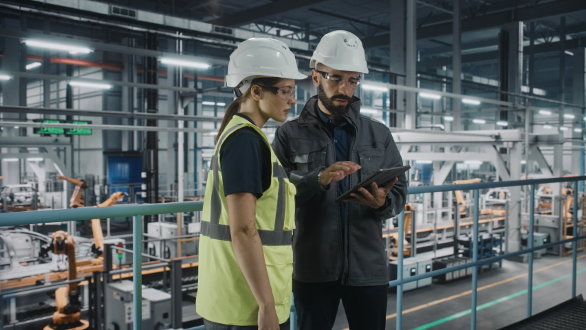 Male Specialist and Female Car Factory Engineer in High Visibility Vests Using Tablet Computer. Automotive Industrial Manufacturing Facility Working on Vehicle Production. Diversity on Assembly Plant.