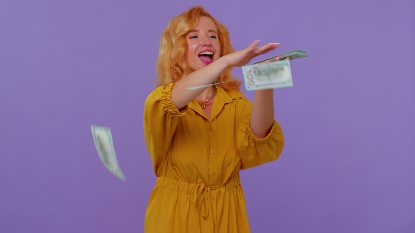 Proud arrogant rich stylish girl showing wasting, spending, scattering, throwing money dollar cash banknotes around with hand, boasting big salary. Woman isolated on purple studio wall background Royalty-Free Stock Footage #1077568715