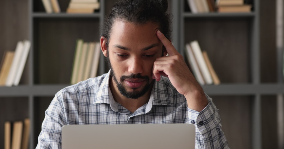 Focused young skilled african american ethnic man working distantly on computer, solving online project problems, creating new ideas, studying on internet courses alone in modern home office. Royalty-Free Stock Footage #1077590327