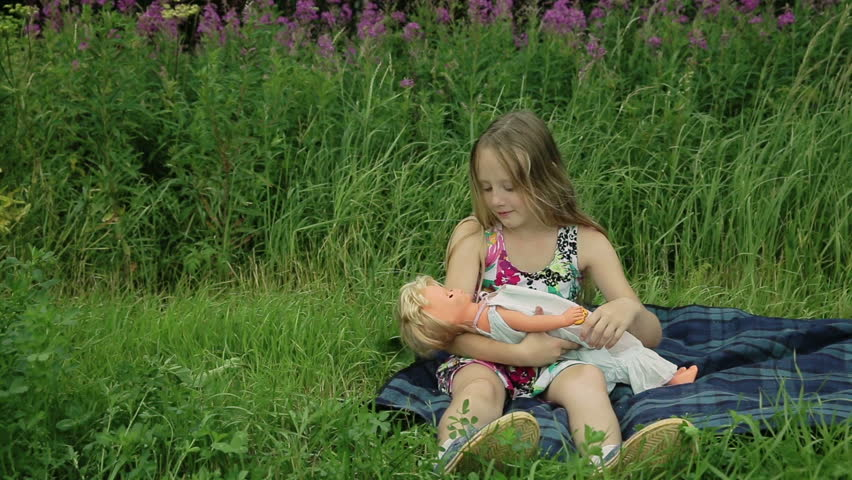 Young girl playing with doll on outside grass | Shutterstock HD Video #10776416