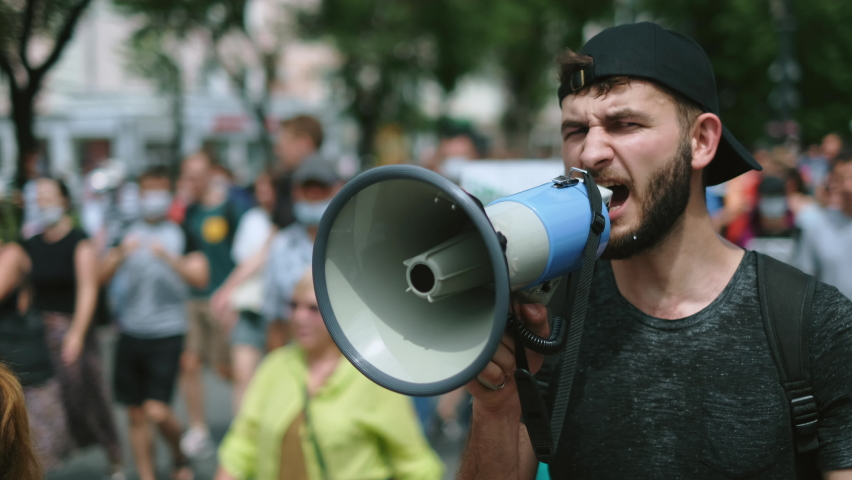 Angry political protester guy with bullhorn marches in protest crowd. Male rebel speaking on demonstration revolt resistance. Strike activist demonstrator man on opposition rally riot with megaphone.
