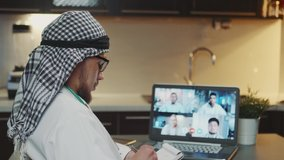 Young Arab economist providing online economical forum with international leaders by video call. He making notes.