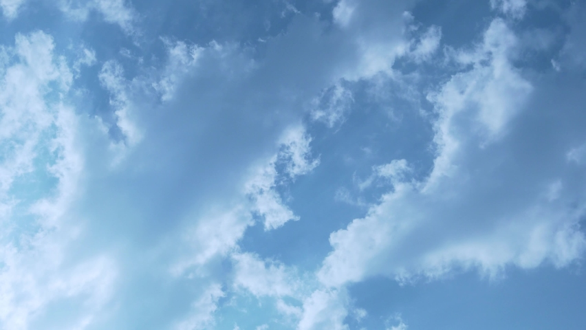 White Flying Puffy Clouds in The Rays Of The Shining Sun in the Blue Sky, Time Lapse. Beautiful Natural Background of Blue Sky and Cumulus Clouds. Sunny Cloudy Sky. Atmosphere, Climate, Meteorology.