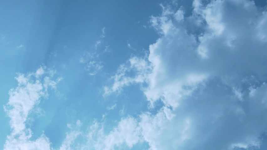 Blue Sky and White Puffy Cumulus Clouds in the Rays of the Sun, Timelapse. The Sun Shines Through White Flying Clouds in A Blue Sky. Beautiful Natural Background of the Sky and Clouds 4K.