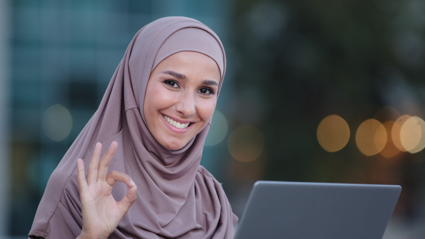 Close-up focused muslim business woman wears hijab works with laptop browsing web in net studying outdoors looking at camera shows ok hand gesture. Islamic girl with computer in city making okay sign Royalty-Free Stock Footage #1078039970