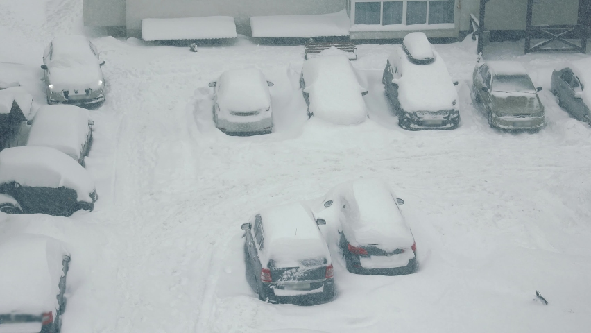 Cars are covered with snow after a snowstorm. Heavy snowfall. Streets and cars are covered with a lot of snow. The car park was covered with heavy snowfalls.