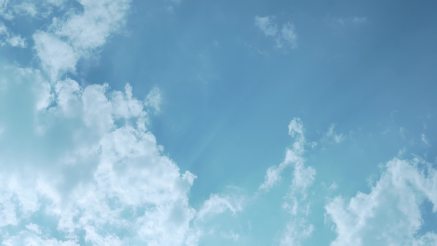 The Sun's Rays Shine Through White Clouds in a Blue Sky, The Time Lapse Of Clouds 4K. Background of Blue Sky and White Clouds in the Sunlight and Glare on a Bright Sunny Day.
