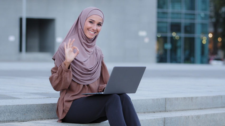 Successful islamic girl muslim young adult woman ethnic female freelancer business student lady wears beige hijab sitting on sidewalk in city uses laptop for distance work browsing shows ok gesture Royalty-Free Stock Footage #1078268939