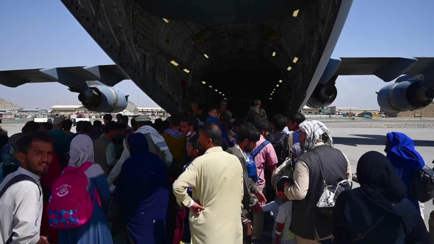 CIRCA 2021 - Afghan refugees attempt to board a U.S. C-17 Globemaster at Hamid Karzai Airport in Kabul Afghanistan during the American evacuation.